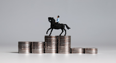 A miniature man riding horses on piles of coins. Three piles of coins in the shape of a podium.