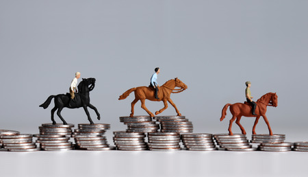 Miniature horse rider on pile of coins. A sports gambling concept. Stock Photo