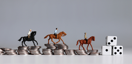 Miniature of horse rider on pile of coins. Concepts about sports gambling and probability of winning or losing. 스톡 콘텐츠