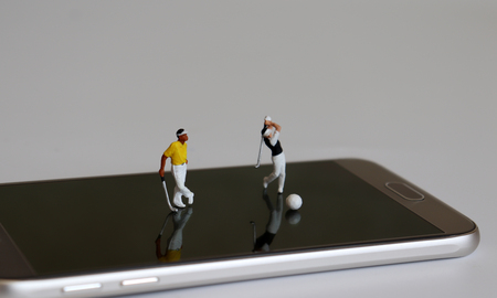 Miniature people playing golf on smart phones.