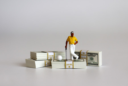 Miniature people playing golf with wad of $ 100 bills. Stok Fotoğraf