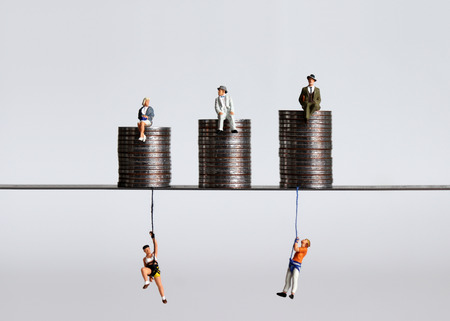 Coin piles and miniature people. A concept of economic imbalance.