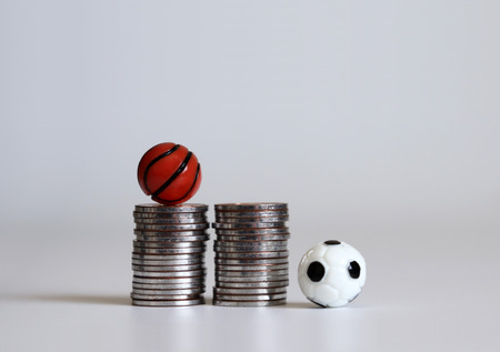 A miniature soccer ball and a basketball ball with pile of coins. Banco de Imagens