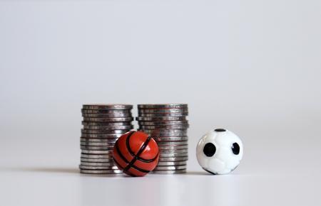 Una pelota de fútbol en miniatura y una pelota de baloncesto con pila de monedas.