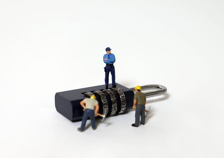 Miniature people standing on the combination lock.