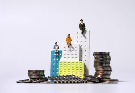 Miniature people sitting on top of a miniature building and pile of coins. Stock fotó