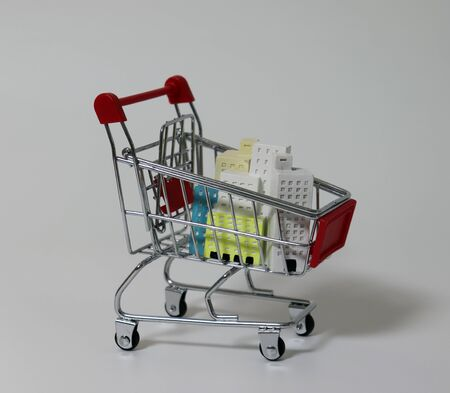 Miniature buildings in shopping cart.