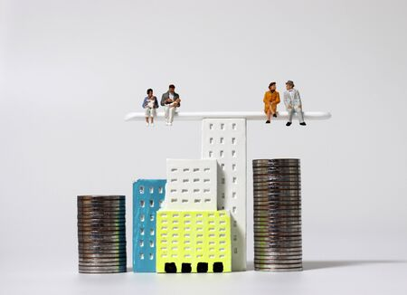Miniature houses and miniature people. The concept is a conflict between the rich and the poor generations. Stock fotó
