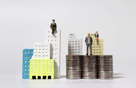 Miniature people sitting on miniature buildings and miniature people standing on piles of coins.