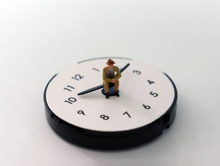 The concept of time management. A miniature man sitting on a clock needle.