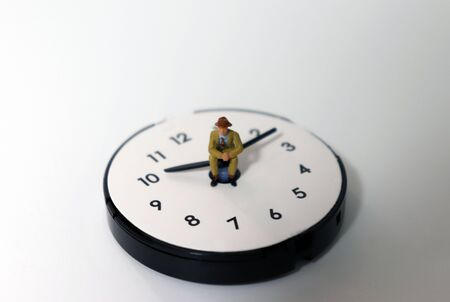 A miniature man sitting on a clock needle. The concept of time management. Foto de archivo - 127508459