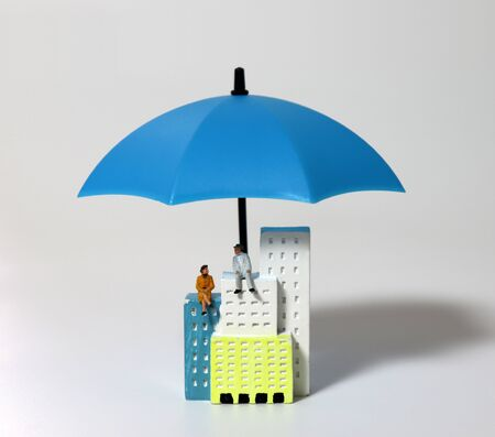 A miniature old couple sitting on a blue umbrella and a building.