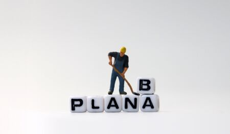 The white cube of PLAN A, B text with miniature people. Zdjęcie Seryjne