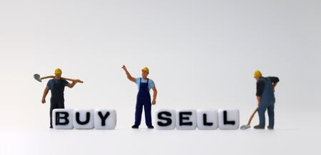 The white cube of 'BUY' and 'SELL' text with miniature people. 免版税图像