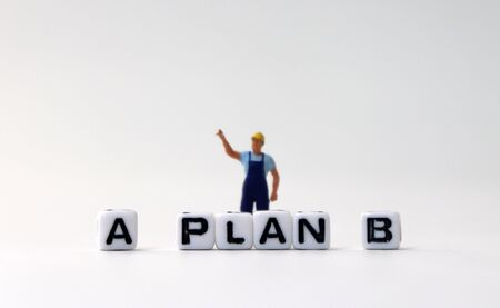 The white cube of 'PLAN A, B' text with miniature people.