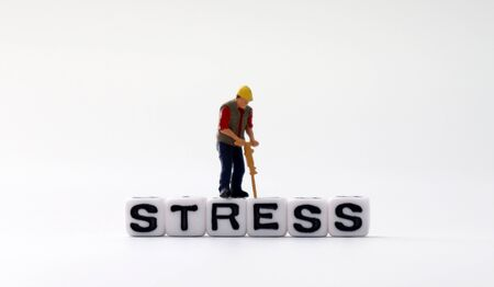 The word STRESS on white cubes with miniature people.