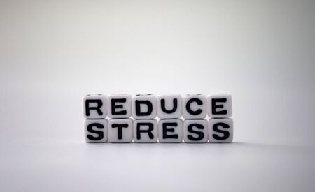 The word STRESS and the word REDUCE on white cubes.
