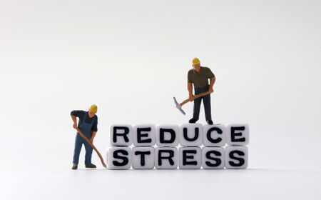 The word STRESS and the word REDUCE on white cubes with miniature people.