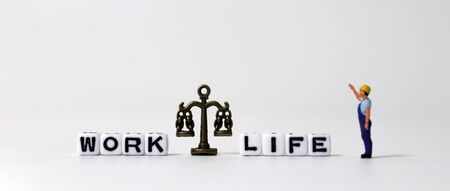 A miniature scale between WORK word and LIFE word on white cubes. The miniature man who is pointing at the cube.