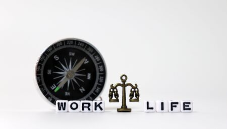 A miniature scale between WORK word and LIFE word on white cubes in front of the compass.