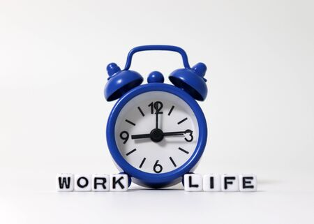 An alarm clock between WORK word and LIFE word on white cubes. Stock fotó