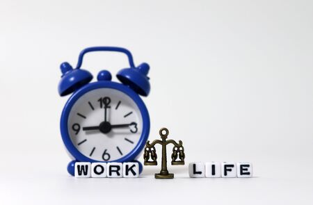 A miniature scale between WORK word and LIFE word on white cubes in front of the alarm clock.