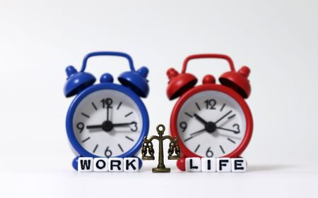 A miniature scale between WORK word and LIFE word on white cubes in front of the two alarm clock.