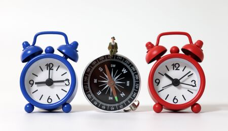 A miniature man sitting on the compass between two alarm clock.