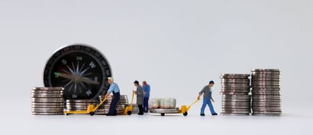 Miniature people carrying coins in a cart and a compass. Stock fotó