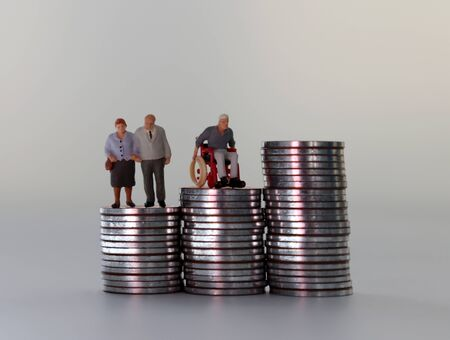 Old age miniature people on pile of coins. Stock fotó