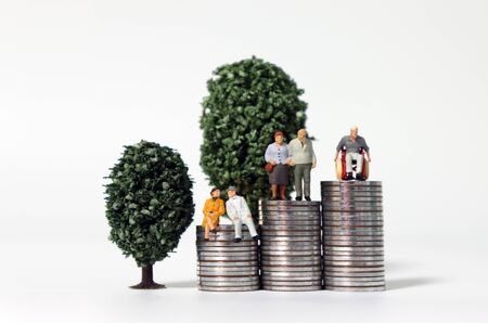 Older miniature people on a pile of coins in front of miniature trees.