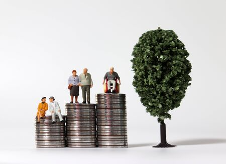Old-age miniature people on a pile of coins with miniature trees. Stock fotó