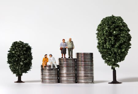 Old age miniature people on a pile of coins between miniature trees.