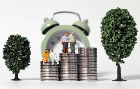 Old age miniature people on a pile of coins between miniature trees coins in front of alarm clock.