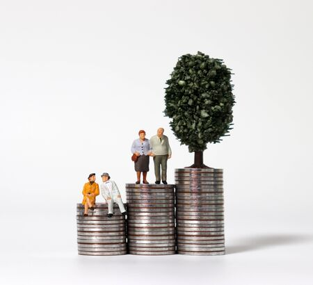 Old age miniature people and a miniature tree on a pile of coins. 免版税图像