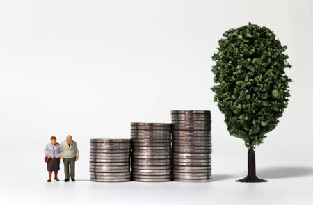 Old age miniature people and a miniature tree with a pile of coins.