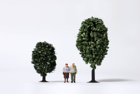 Old age miniature people walking between miniature trees.