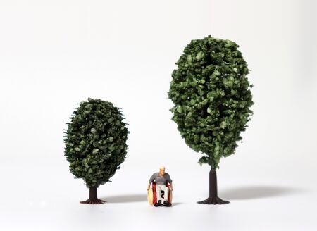 A miniature man in a wheelchair between miniature trees. 版權商用圖片