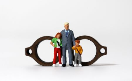 Miniature single daddy and children standing in front of wooden miniature glasses.