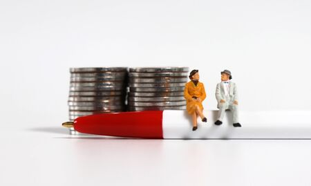 A miniature old couple sitting in a red ball pen in front of a pile of coins.