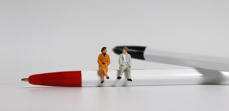 A miniature old couple sitting on a red ballpoint pen with a black ball pen. 免版税图像