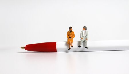 A miniature old couple sitting on a red ballpoint pen.