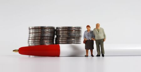 A miniature old couple standing with a red ball pen in front of a pile of coins.