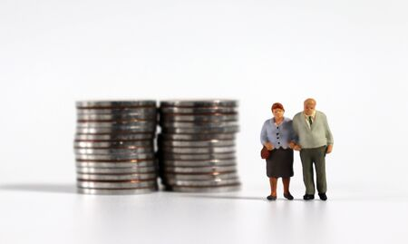 A miniature old couple standing next to a pile of coins. 免版税图像