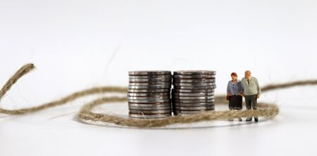 A miniature old couple standing with a rope next to a pile of coins.