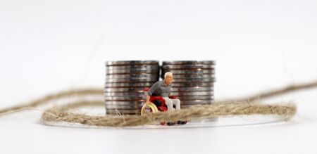 A miniature man in a wheelchair in a rope with a pile of coins. 免版税图像