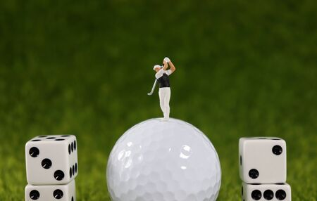 A miniature golfer who is swinging on a white golf ball between dice.