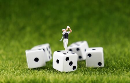 A miniature golfer on a dice with a lawn background.