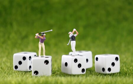 Two miniature golfers on white dice with a lawn background.