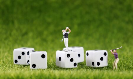 Two miniature golfers and five white dice with a lawn background. Stock Photo